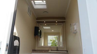 The interior lighting & vanity mirror of our 3 Stall Portable Luxury Restroom Trailer Rental