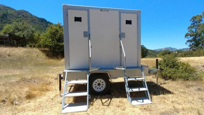 A small luxury flushing restroom trailer in a field near Petaluma, CA.